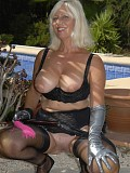 Wild blonde milf posing in sexy black stockings with a whip in her hands