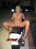 Blonde cougar with huge cans poses in a small bikini while riding on a bike