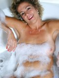 Watch horny mom take a bubble bath with a glass of wine and fuck her hairy hole