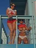 Two amazing cougars dressed as lifeguards flash their tits at a public beach