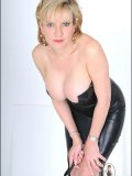 Busty domme dressed in a gorgeous black leather dress highlighting her breasts