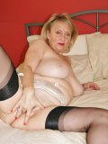Mature babe in black stockings steps up in front of mirror and tortures her clit