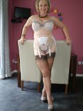 Curvaceous old lady shows the sexy lingerie and stockings hiding under her dress
