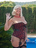 Ravishing blonde mature milf flaunts her sexy body in a tight corset by the pool
