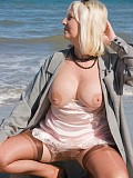 Naughty blonde milf loves to pose on the beach taking her bra off and flaunting her tits