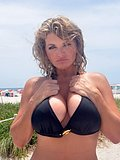 Kinky blonde cougar flashes her massive tits and hot pink pussy at the beach