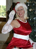 Naughty blonde housewife posing as a kinky Mrs. Santa in silky red lingerie