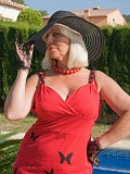 Sassy blonde milf posing by the pool in red high heels and a laced corset that flaunts her hot body