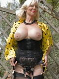 Amazing pictures of a horny mature milf posing on the grass with her bare tits