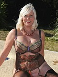 Naughty blonde mature housewife posing on her balcony wearing sexy stockings
