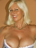 Sassy blonde milf loves to tease posing on the bed wearing just her tight corset
