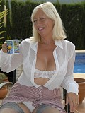 Incredibly hot pictures of a sexy mature blonde flaunting her big ass in white stockings