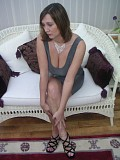 Glamorous mature brunette teases in a short dress and high heels before stripping