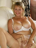 Gorgeous mature blonde posing naked while fingering her juicy pussy