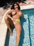 Slutty brunette cougar spreads her sexy pussy wide open by the pool