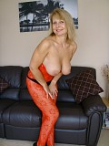 Mature hottie posing in an incredibly sexy pair of red see through stockings and flashing her cunt